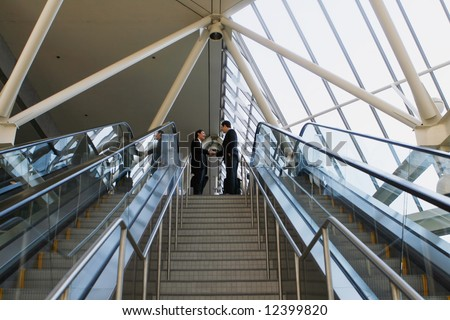 Panoramic shot of two businessmen shaking hands at the top of a stairway - stock photo