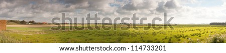 Panoramic shot of typical Dutch farmland with farm and blue stormy cloudy sky. Dunes in the background. Texel. Wadden island. The Netherlands. - stock photo