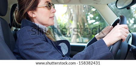 Panoramic side portrait view of a mature middle aged smart woman sitting on the drivers seat of a new car, driving through a countryside road during a sunny winter day. - stock photo