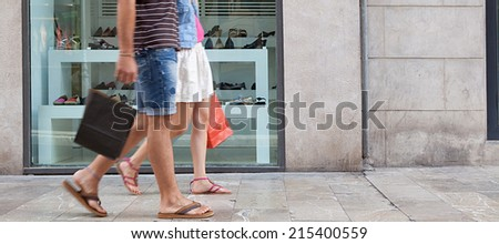 Panoramic side view of a couple lower body section walking in shopping street with a shoe store window display, carrying shopping bags and spending money on holiday. Consumer lifestyle, outdoors. - stock photo