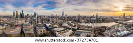 Panoramic skyline of east and south London at sunset. This wide view includes the famous financial Bank district, famous skyscrapers, Tate modern, River Thames and the Millennium Wheel - London, UK - stock photo