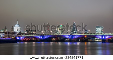 Panoramic skyline of London seen from the river Thames at sunset on an overcast day. The skyline includes St. Paul's Cathedral, Blackfriars Bridge, 122 Leadenhall Street and 20 Fenchurch Street. - stock photo