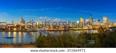 Panoramic skyline of St. Paul's Cathedral, Millennium Bridge and financial Bank district of London at dusk - UK - stock photo
