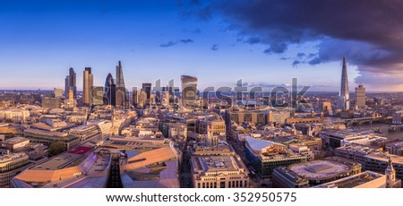 Panoramic skyline of the famous business district of London at sunset with dark clouds - London, UK - stock photo