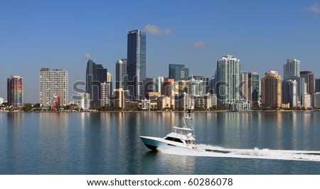 Panoramic Skyline view of Miami and Biscayne Bay from the Key Biscayne Bridge with fishing yacht cruising by. - stock photo