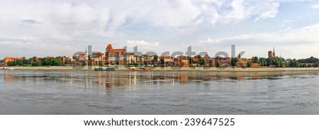 Panoramic skyline view of Torun old town reflected in Vistula river, Poland - stock photo