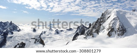 Panoramic snowy high mountains climb landscape with cloudy sky - stock photo
