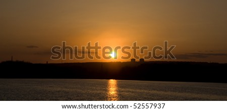 panoramic sunset above the town and lake - stock photo
