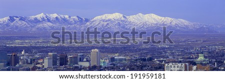 Panoramic sunset of Salt Lake City with snow capped Wasatch Mountains - stock photo