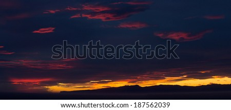 Panoramic sunset over the coast of New Zealand as the sun illuminates the clouds with brilliants reds and oranges with the ocean providing foreground - stock photo
