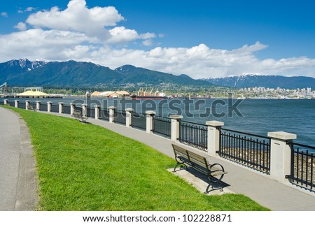 Panoramic view at the gorgeous sea walk with some benches in the park. Vancouver, Canada. - stock photo