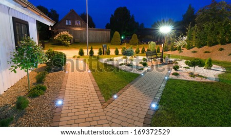 Panoramic view for modern villa garden at night - stock photo