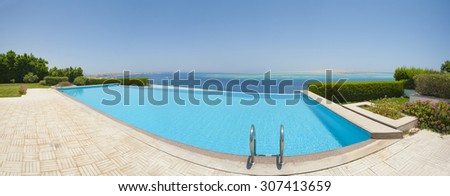 Panoramic view from a luxury infinity swimming pool with tropical sea outlook - stock photo