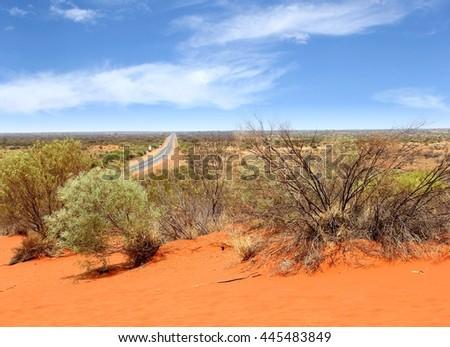 Panoramic view from above of Lasseter Highway to Uluru Ayers Rock between red sand dunes, Australia. - stock photo