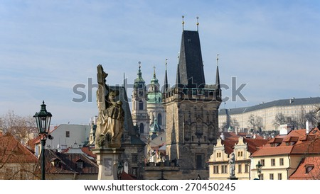 Panoramic view from Charles Bridge toward Lesser Town towers, Saint Nicholas Cathedral and Prague Castle with statues of St. Luthgard on foreground, Czech Republic. - stock photo