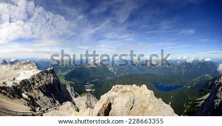 Panoramic view from mountain station at the Zugspitze in summer. The Zugspitze, at 2,962 meters above sea level, is the highest mountain in Germany. - stock photo
