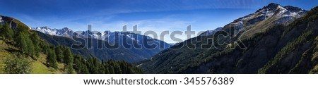 Panoramic view from mountain top spring in the alpine mountain range. View to the high peaks and a valley. - stock photo