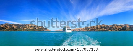 Panoramic view from the banks of Akaroa at the ship anchored nearby - stock photo