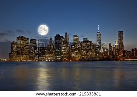 Panoramic view New York City Manhattan downtown skyline at night with skyscrapers and bright full moon - stock photo