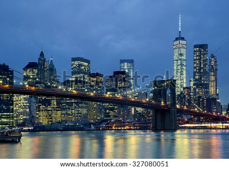 Panoramic view new york city manhattan downtown skyline at night with skyscrapers and brooklyn bridge - stock photo