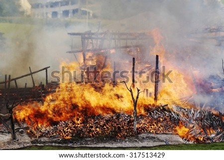 Panoramic view of a a complete destruction of a wooden house after a fire. Blazing fire burns through the roof rafters of an old farm home on a mountain resort - stock photo