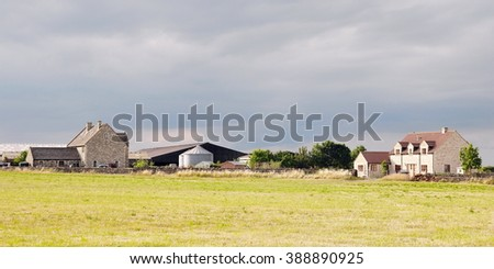 Panoramic View of a Farm and Green Field in Rural England - stock photo