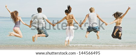 Panoramic view of a group of five friends holding hands and jumping at once on a golden sand beach against a blue sea and sky, expressing energy, fun and joy during their summer vacation. - stock photo