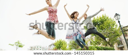 Panoramic view of a group of three friends jumping up in the air together while visiting an urban park in the city, having fun and enjoying the energy during a summer day on vacation. - stock photo