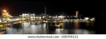 Panoramic view of a large offshore oil platform at night - stock photo