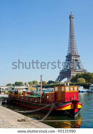 Panoramic view of a red living barge on the Seine in Paris with Eiffel tower background. France - stock photo