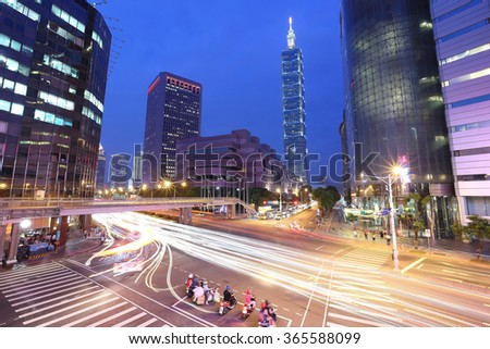 Panoramic view of a street corner in Taipei City with busy traffic trails at rush hour ~ Beautiful night scenery of Taipei 101 Tower and World Trade Center in XinYi commercial area in Taipei downtown
