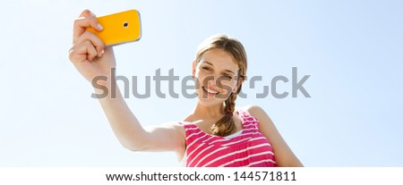 Panoramic view of a teenager girl using her smartphone to take photographs while standing against an intense blue sky background, smiling and having fun. - stock photo