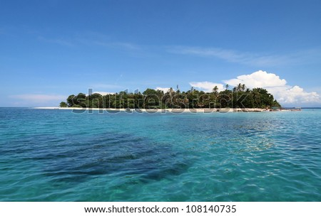 Panoramic view of a tropical island with lush vegetation and boat tour landed on the beach, Caribbean sea, Panama - stock photo