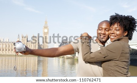 Panoramic view of a young african american couple taking pictures of themselves while on vacations in London, standing in front of Big Ben.