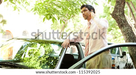 Panoramic view of a young successful businessman with his car having a phone conversation using a hands free set in a tree lined street in the city. - stock photo