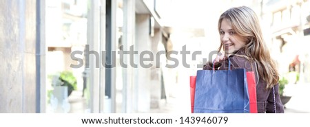 Panoramic view of a young woman walking and shopping in the city, turning to smile at camera while carrying paper bags over her shoulder, joyful and smiling. - stock photo