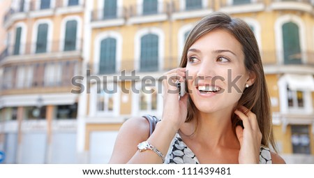 Panoramic view of an attractive businesswoman having a conversation on her cell phone while outdoors, surrounded by classic uniform architecture. - stock photo