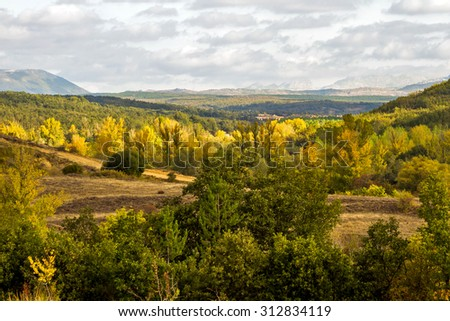 Panoramic view of beautiful rolling autumn landscape with forests of oaks, pines and poplars. Wide visibility that reveals the background mountains  - stock photo