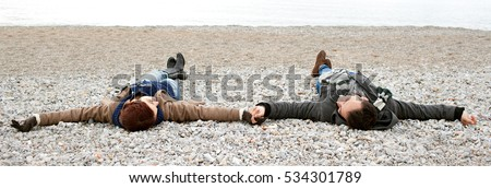 Panoramic view of beautiful tourist couple lying on pebble beach, smiling holding hands, on winter holiday, nature textures outdoors. Man and woman romantic fun, lifestyle coastal exterior.