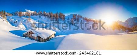 Panoramic view of beautiful winter mountain landscape with traditional mountain cabin in the Alps in golden evening light at sunset - stock photo