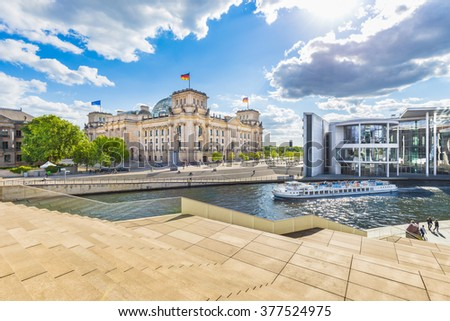 Panoramic view of Berlin government district with excursion boat on Spree river passing famous Reichstag building and Paul Lobe Haus on a sunny day with blue sky and clouds, Berlin Mitte, Germany - stock photo