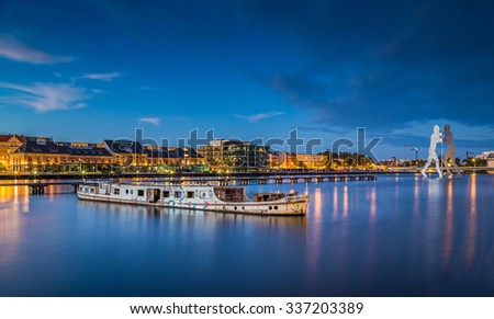 Panoramic view of Berlin skyline with famous Molecule Man sculpture and old abandoned ship wreck lying in river Spree in twilight during blue hour at dusk, Berlin Friedrichshain-Kreuzberg, Germany - stock photo