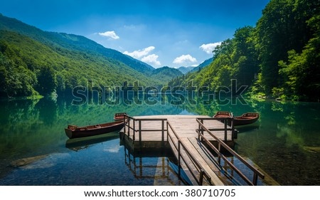 Panoramic view of Biogradsko lake. Virgin forests and beautiful mountains, wooden pier and boats. National park Biogradska gora is very popular touristic destination in Montenegro.