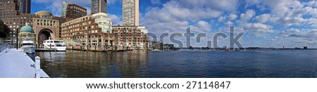 panoramic view of boston harbor with rowes wharf and skyscraper buildings in boston massachusetts on a cloudy winter day - stock photo