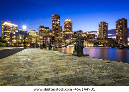 Panoramic view of Boston in Massachusetts, USA at night showcasing the skyscrapers of its Financial District and the Boston Harbor. - stock photo