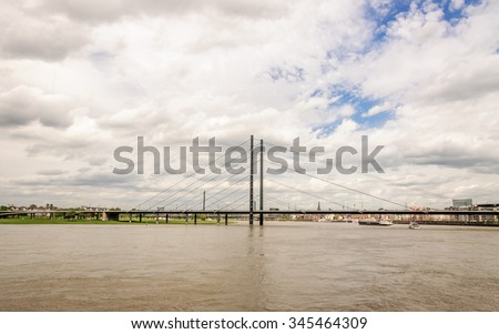 Panoramic view of bridge across the Rhine, river and grey clouds in blue sky. Bridge located in close proximity to the historical part of the city and promenade of Dusseldorf, Germany - stock photo