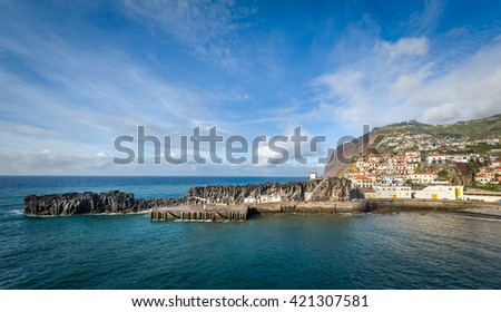 Panoramic view of Camara de Lobos fishing village harbor. Old town buildings, pier and small lighthouse on the rocky shore of Atlantic ocean. Madeira island, Portugal. - stock photo