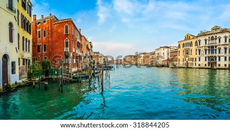 Panoramic view of Canal Grande with colorful houses and famous Rialto Bridge in the background in Venice, Italy - stock photo