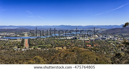Panoramic view of Canberra city downtown and capital hill from Mt Ainslie on a sunny bright day when sky is deep and blue and town is calm.