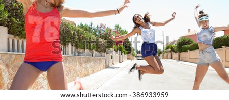Panoramic view of diverse joyful teenagers girls friends having fun together in a suburban home exterior street jumping with energy in sunny outdoors. Sporty action. Adolescents on holiday, smiling. - stock photo
